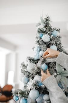 Chiuda sull'immagine della donna in maglione che decora l'albero di natale con le bagattelle