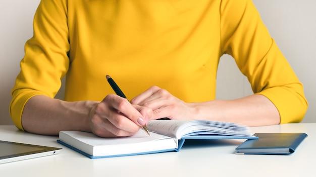 Immagine ravvicinata di una donna in un abito giallo seduto a una scrivania in ufficio e scrivere qualcosa in un taccuino in bianco bianco