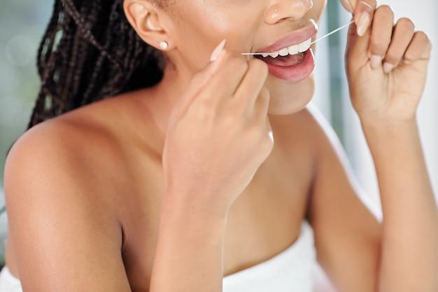 Immagine ravvicinata della giovane donna nera utilizzando il filo interdentale dopo aver preso la doccia serale