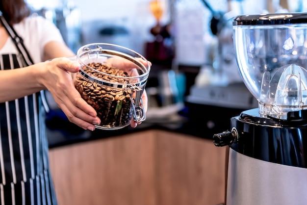 Immagini ravvicinate del proprietario della caffetteria mostra i chicchi di caffè di qualità che vengono tostati e cotti