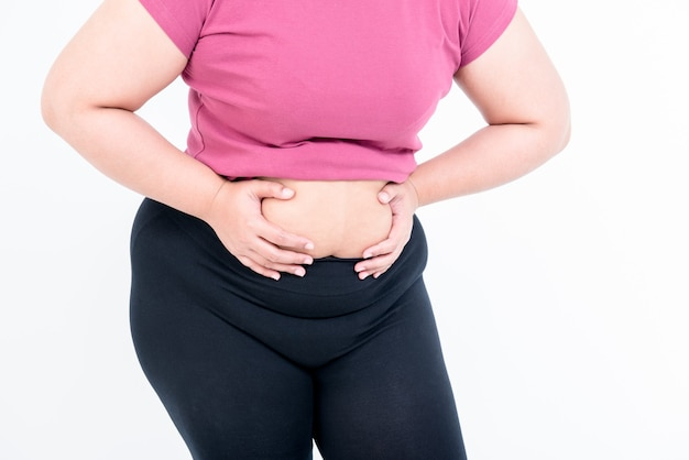 Chiudere le immagini della donna grassa utilizzando entrambe le mani per afferrare il grasso della pancia che ha le sue dimensioni, su sfondo bianco, alla donna grassa e al concetto di assistenza sanitaria.