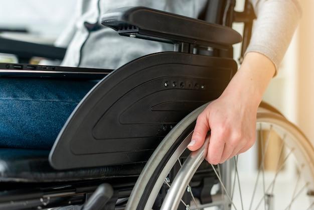 Individuale del primo piano che si tiene per mano sulla sedia a rotelle