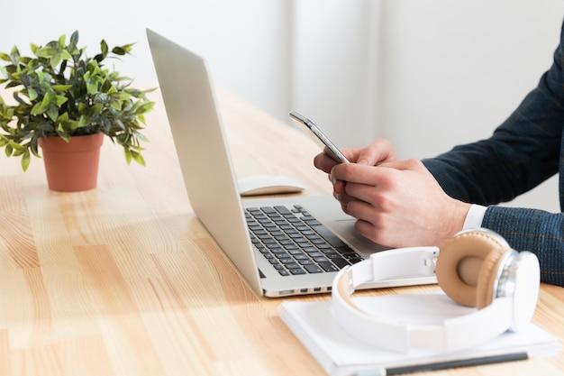 Individuo del primo piano che lavora al computer portatile
