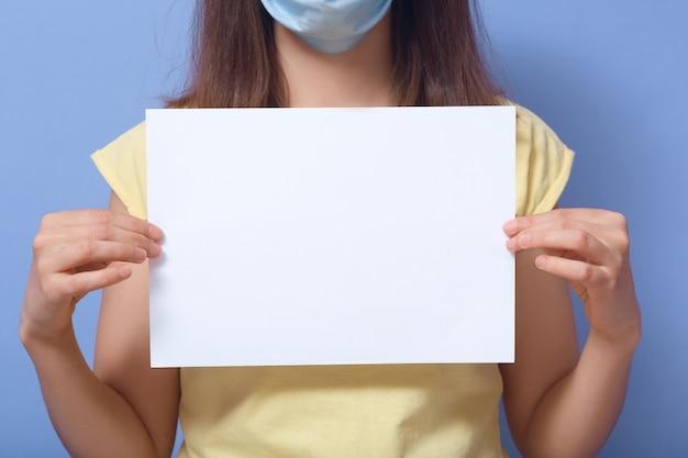 Chiuda sull'immagine dell'interno della femmina in maglietta gialla e maschera facciale, tenendo il foglio di carta per il testo, portando il messaggio, copyspace per la pubblicità, zona di informazioni. concetto di persone e logo