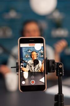 Primo piano dell'influencer vlogger registrare la trasmissione in diretta guardando lo smartphone su treppiede a casa studio podcast. creatore di contenuti creativi che realizza video online per il pubblico degli abbonati