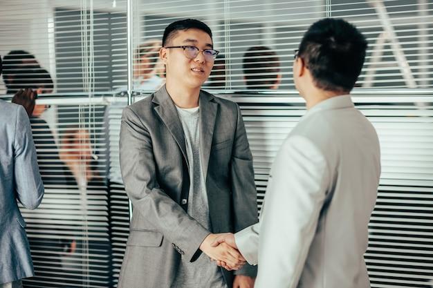 Avvicinamento. partner commerciali internazionali si salutano con una stretta di mano.