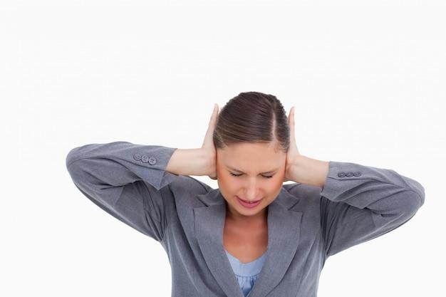 Chiuda in su del tradeswoman irritato che copre le sue orecchie