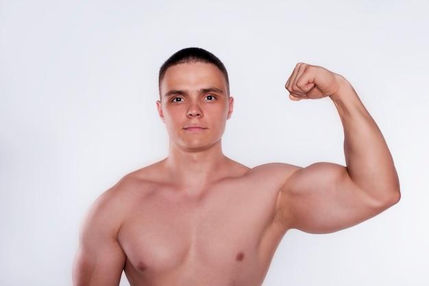 Chiuda sulla foto isolata del bodybuilder muscolare nudo bello forte su bianco