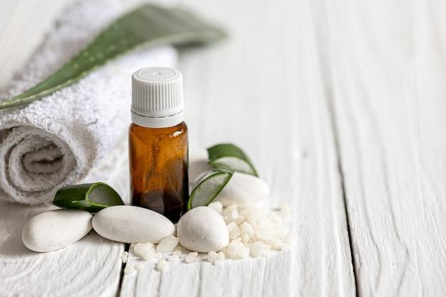 Primo piano di un barattolo con olio naturale per la bellezza e la salute sullo sfondo delle foglie di aloe con uno spazio copia asciugamano.