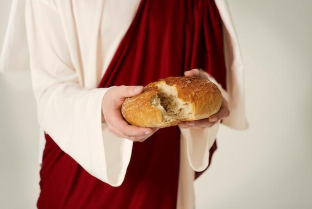 Primo piano delle mani di gesù con il pane della vita Foto Premium