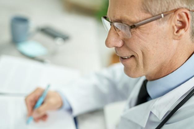 Primo piano di un lavoratore medico gioioso che tiene in mano una penna e sorride mentre è seduto al tavolo al lavoro