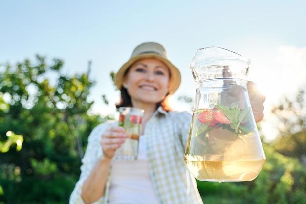 Primo piano della brocca e del vetro con la bevanda della fragola della menta alle erbe naturali nelle mani della donna. bevande rinfrescanti fredde estive, sane bevande vitaminiche fatte in casa