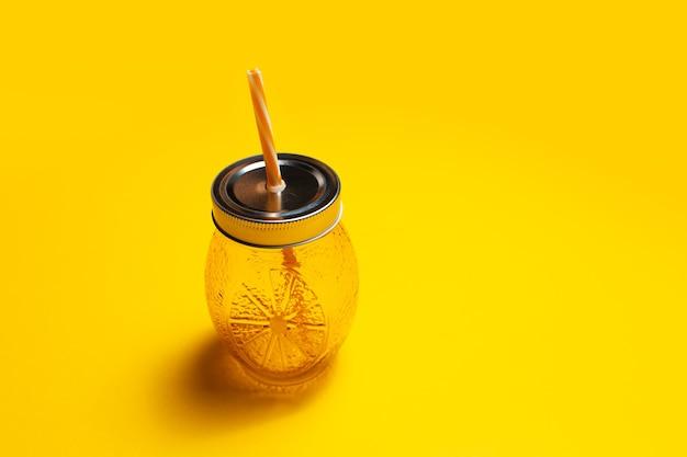 Close-up di succo di tazza di vetro di colore arancione, con paglia e tappo in acciaio,