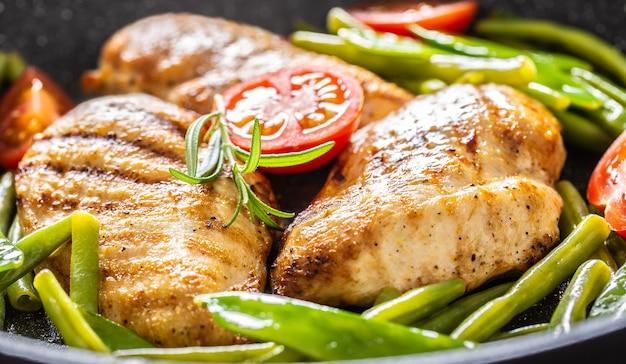 Close up di succosi petti di pollo, piselli primaverili, fagiolini e pomodorini in una padella con pepe nero e condimento di rosmarino fresco.