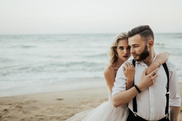 Chiuda in su della coppia appena sposata che sta fuori e che abbraccia.