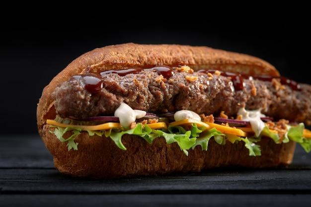 Chiuda su del panino di kebab su fondo di legno nero