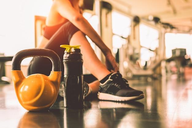 Chiuda sui kettlebells con l'allenamento di esercizio della donna nella rottura di forma fisica della palestra rilassi dopo lo sport