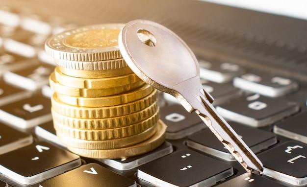 Primo piano della chiave e della pila di monete sulla tastiera nera. concetto di assicurazione