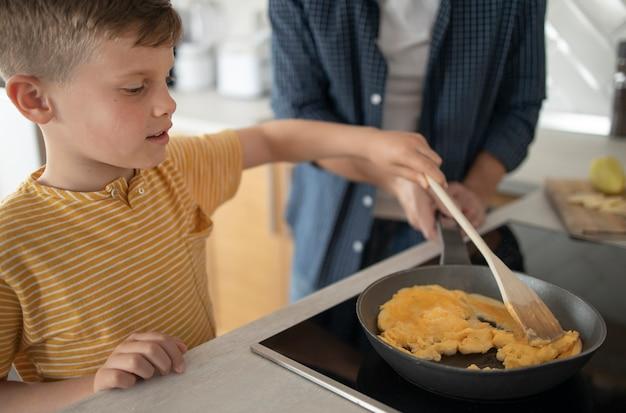 Chiuda sul bambino che cucina l'omelette