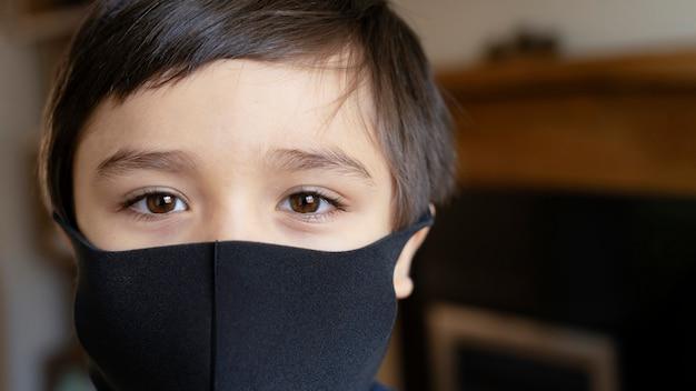 Primo piano volto di un bambino che indossa una maschera medica, ragazzo di razza mista con bellissimi occhi marroni maschera nera, ragazzino stare a casa durante il blocco covid-19.