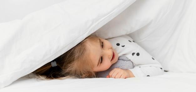 Bambino del primo piano che si nasconde sotto la coperta