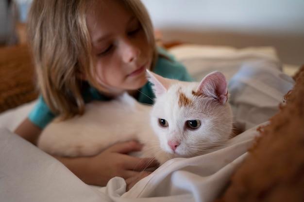 Primo piano bambino che tiene in mano un simpatico gatto bianco
