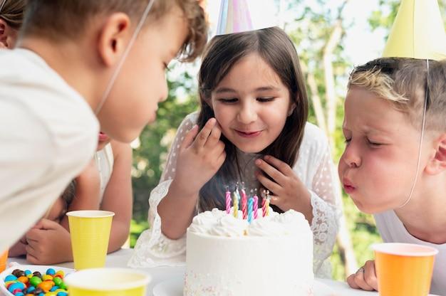 Bambini ravvicinati che spengono le candeline
