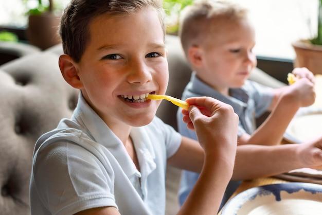 Chiudere i bambini che mangiano patatine fritte