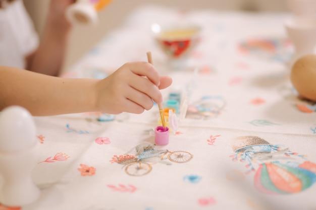 Chiuda in su della mano di bambini utilizzando un pennello per dipingere l'umore pasquale