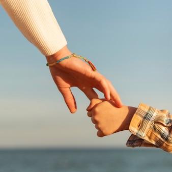 Bambini del primo piano che tengono le mani in riva al mare