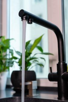 Primo piano su un rubinetto della cucina con acqua corrente su uno sfondo di piante verdi in vaso sul davanzale di una finestra