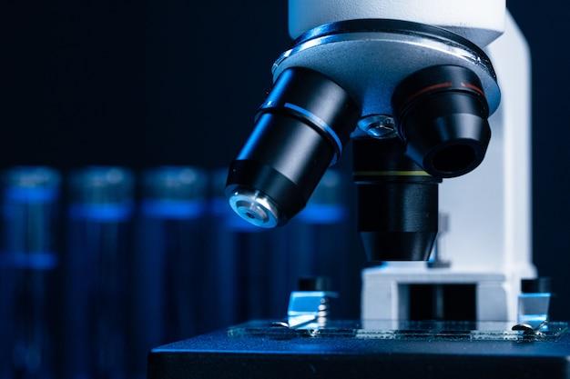 Chiuda in su del microscopio del laboratorio con l'insieme delle provette con liquido blu