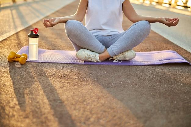 Primo piano di una donna in abiti sportivi seduta nella posizione del loto e che fa esercizi di meditazione yoga all'aperto