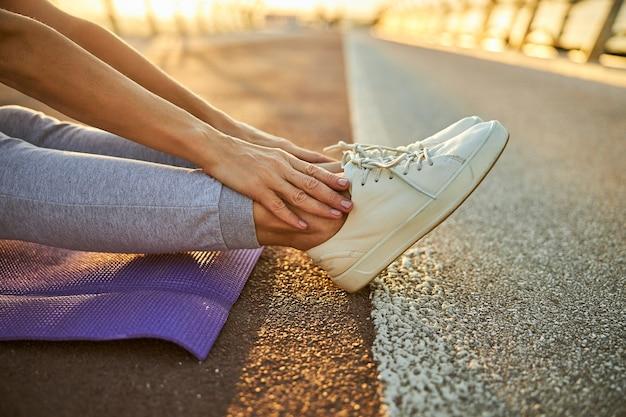 Primo piano di una signora con scarpe sportive bianche che le toccano le gambe mentre riposa sulla strada asfaltata