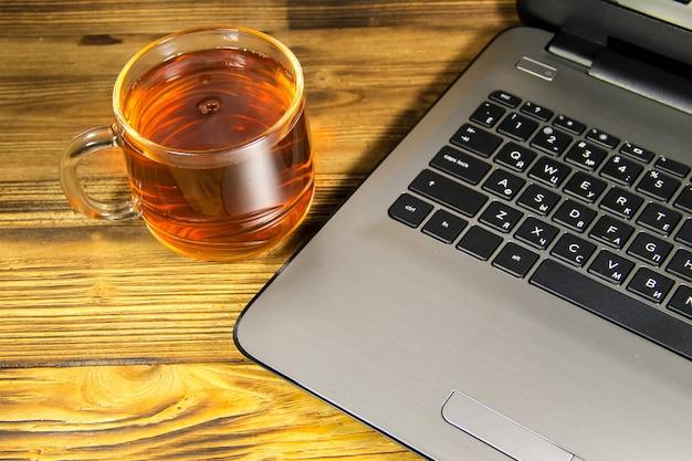 Primo piano del computer portatile e della tazza di tè sulla tavola di legno