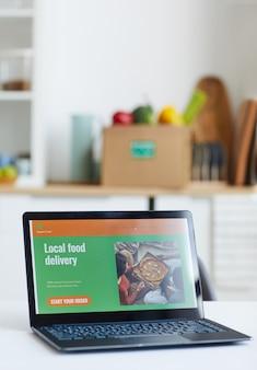 Primo piano del computer portatile sul tavolo con il sito web di consegna di cibo locale