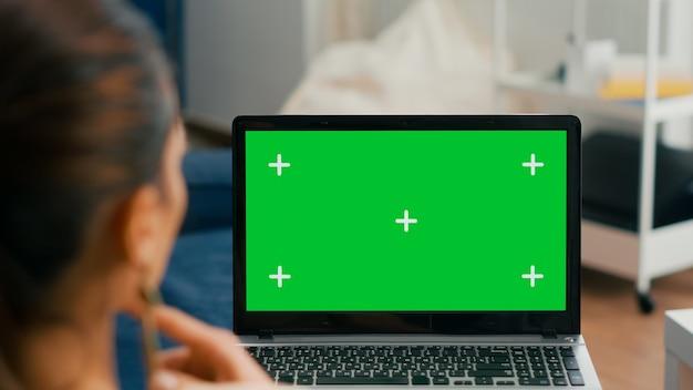Chiuda in su del computer portatile con mock up display chroma key schermo verde. donna d'affari sdraiata sul divano e digitando su un pc isolato per un progetto commerciale in ufficio a casa