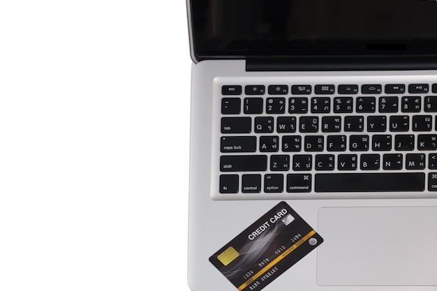 Vista superiore del computer portatile e della carta di credito del primo piano libera dallo spazio della copia. acquisti / pagamenti online utilizzando il concetto.