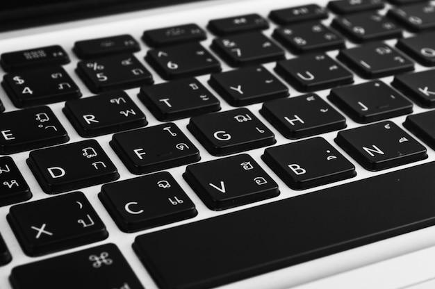 Chiuda sulla tastiera del computer portatile con la lingua inglese tailandese di un computer portatile moderno