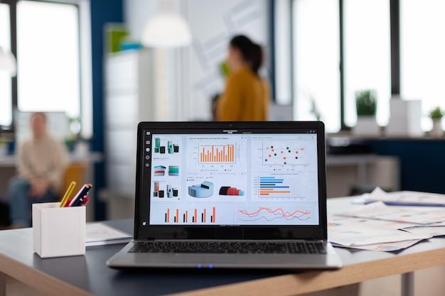 Primo piano del computer portatile nell'ufficio della società di avvio con grafici e statistiche. area di lavoro nel centro affari con dipendenti multietnici, inquadratura di una stanza con mobili moderni e parete blu.