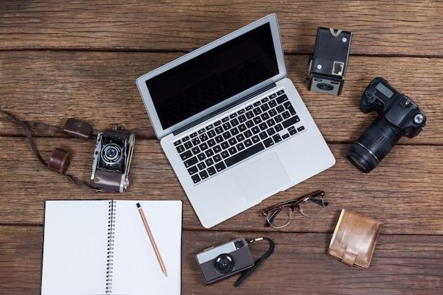 Primo piano del computer portatile con le macchine fotografiche sulla tavola