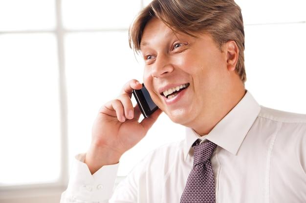 Primo piano di un uomo d'affari che ride al telefono nel suo ufficio