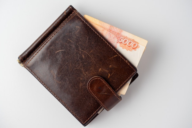 Un primo piano di un portafoglio in pelle pieno di banconote da 5000 rubli giace su uno sfondo bianco. vista dall'alto, posizione piatta