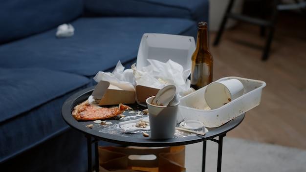 Primo piano di cibo avanzato sul tavolo in un soggiorno vuoto e disordinato