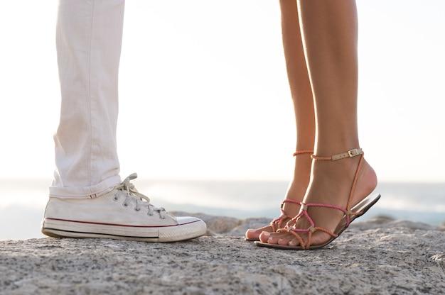 Chiuda in su delle gambe delle coppie che si baciano su una roccia in mare