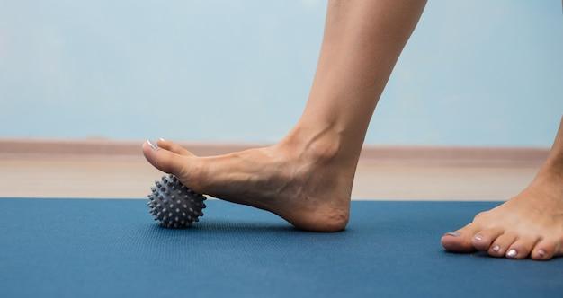 Primo piano delle gambe che rotolano una palla da massaggio grigia su uno sfondo blu con un posto per il testo