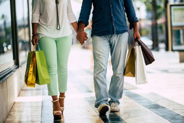 Primo piano delle gambe di due adulti che camminano in un centro commerciale con cinque borse della spesa con vestiti su di esso - relazione tra uomo e donna insieme che vanno a comprare vestiti