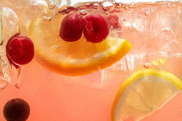 Primo piano di fette di limone e ciliegia nella parete di limonata e cubetti di ghiaccio.