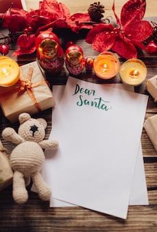 Primo piano di una lettera per babbo natale circondato da doni