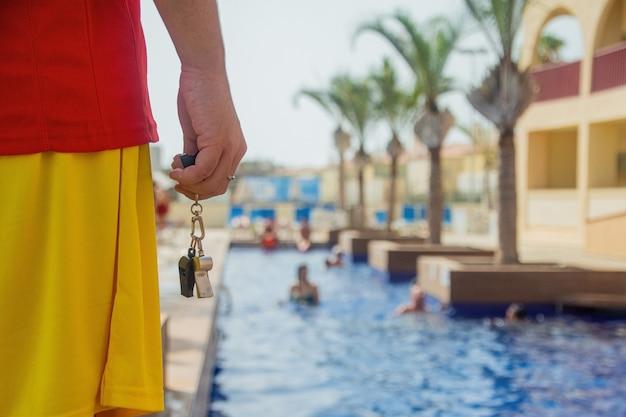 Primo piano della mano di un bagnino che tiene un fischietto e che veglia su una piscina - concetto di bagnino al lavoro.